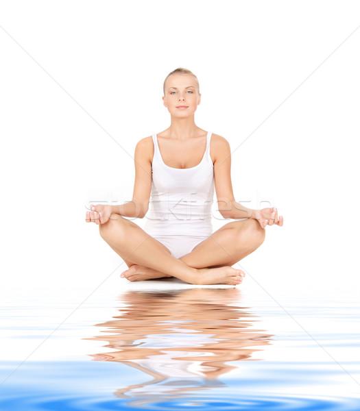 woman practicing lotus pose on white sand Stock photo © dolgachov