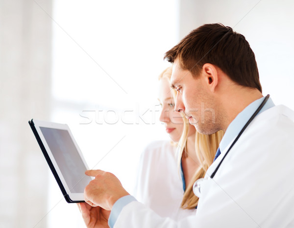 two doctors looking at x-ray on tablet pc Stock photo © dolgachov
