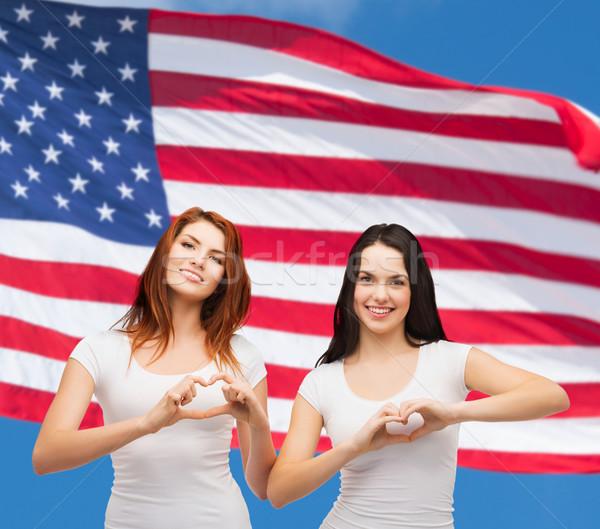 Dos sonriendo ninas corazón manos Foto stock © dolgachov