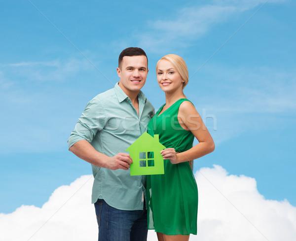smiling couple holding green paper house Stock photo © dolgachov