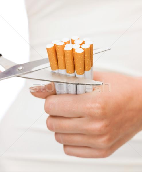 close up of scissors cutting many cigarettes Stock photo © dolgachov