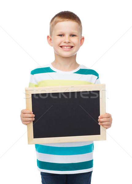Mosolyog kicsi fiú tart fekete tábla Stock fotó © dolgachov