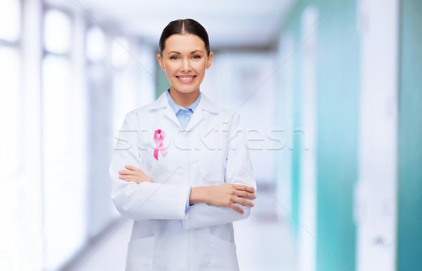 smiling female doctor with cancer awareness ribbon Stock photo © dolgachov