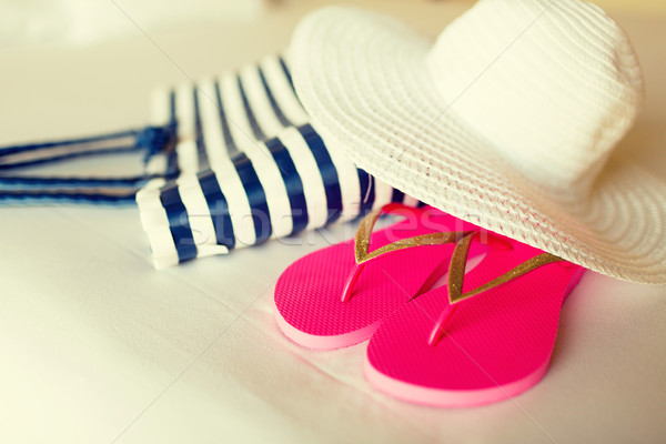 close-up of beach bag, hat and flip-flops on bed Stock photo © dolgachov