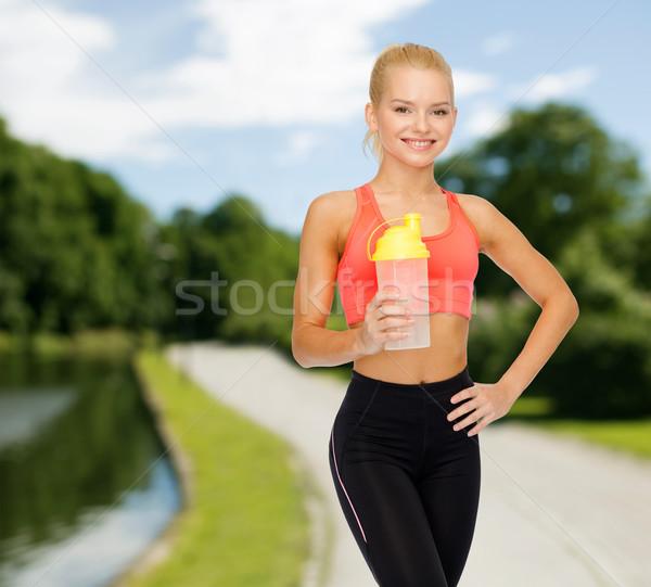Sorridere donna proteine shake bottiglia Foto d'archivio © dolgachov