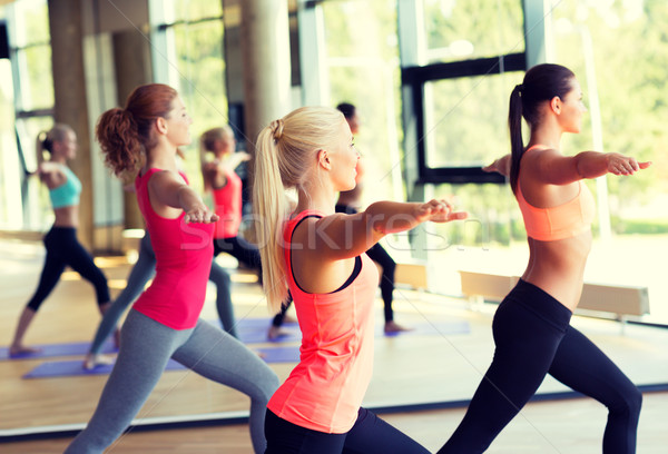 group of smiling women stretching in gym Stock photo © dolgachov