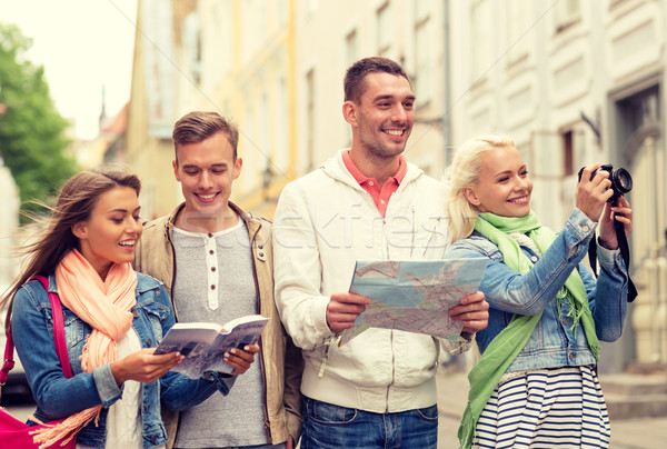 group of friends with city guide, map and camera Stock photo © dolgachov