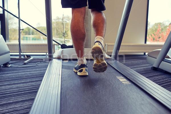 Közelkép férfi lábak sétál futópad tornaterem Stock fotó © dolgachov