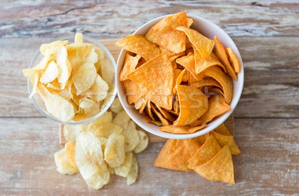 close up of potato crisps and corn nachos on table Stock photo © dolgachov