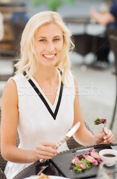 happy woman eating dinner at restaurant terrace Stock photo © dolgachov