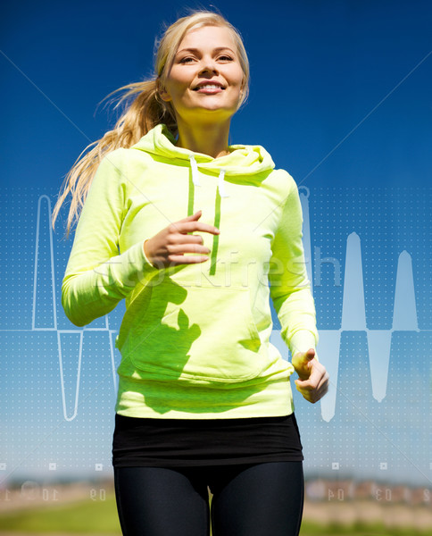 smiling woman jogging outdoors Stock photo © dolgachov