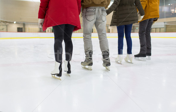 Stock photo: close up of happy friends skating on ice rink