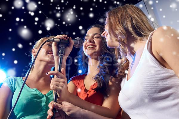 Feliz mulheres jovens cantando karaoke boate festa Foto stock © dolgachov
