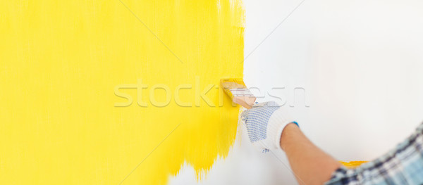 close up of male in gloves painting a wall Stock photo © dolgachov