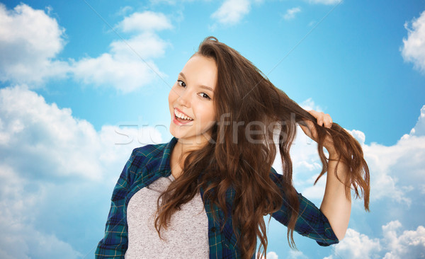happy teenage girl holding strand of her hair Stock photo © dolgachov