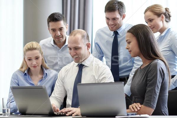 Lächelnd Geschäftsleute Laptops Büro Geschäftsleute Technologie Stock foto © dolgachov