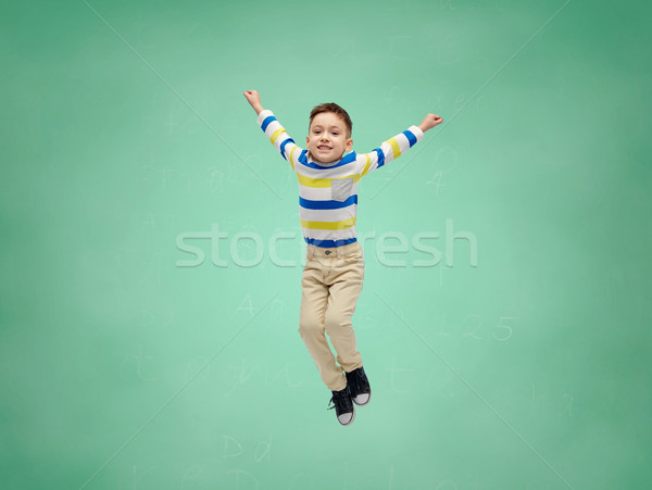 happy little boy jumping in air over school board Stock photo © dolgachov