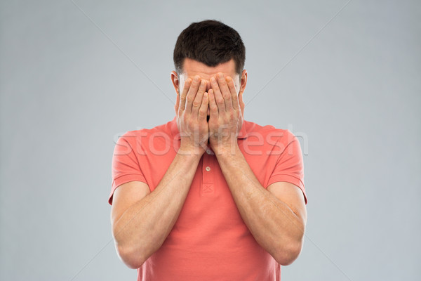 man in t-shirt covering his face with hands Stock photo © dolgachov