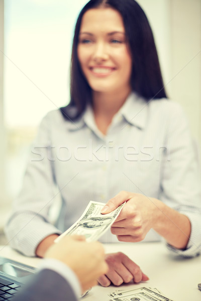 Stock photo: close up of happy woman giving or exchanging money