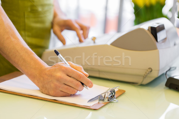 close up of man with clipboard at flower shop Stock photo © dolgachov