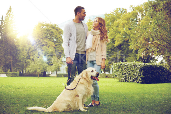 happy couple with labrador dog walking in city Stock photo © dolgachov