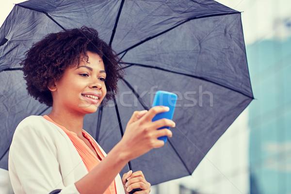 Zakenvrouw paraplu smartphone business slechte weer Stockfoto © dolgachov