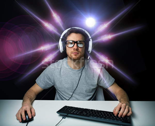 man in headset playing computer video game Stock photo © dolgachov