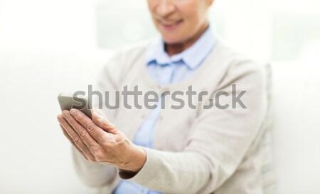 close up of senior woman with smartphone texting Stock photo © dolgachov