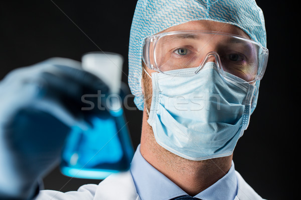 close up of scientist holding flask with chemical Stock photo © dolgachov