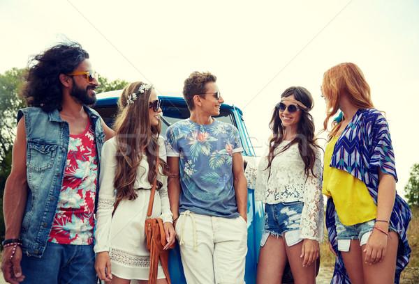 smiling young hippie friends over minivan car Stock photo © dolgachov