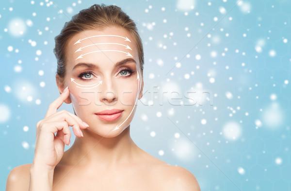 Gyönyörű fiatal nő emel nyilak arc szépség Stock fotó © dolgachov