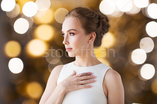 woman in white with diamond ring and earring Stock photo © dolgachov