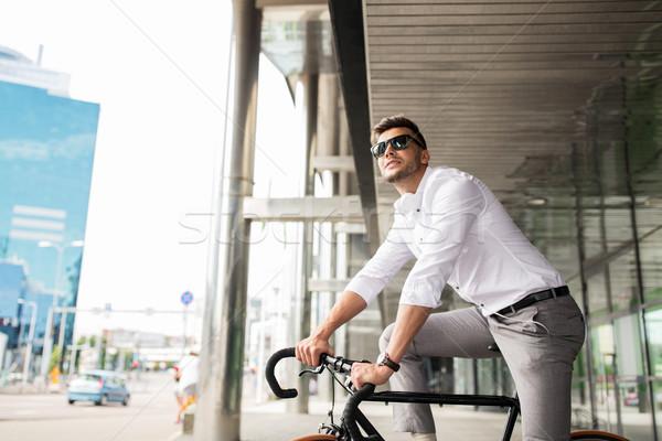man with bicycle and headphones on city street Stock photo © dolgachov