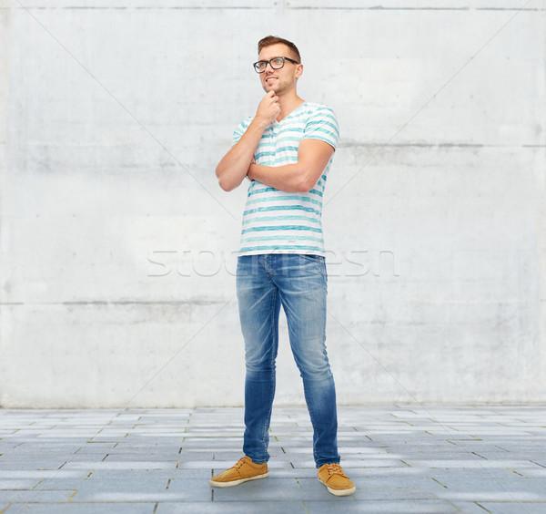 smiling young man in eyeglasses thinking Stock photo © dolgachov