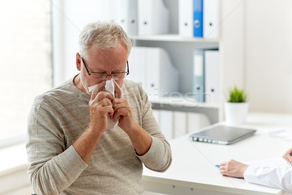 senior man blowing nose with napkin at hospital Stock photo © dolgachov