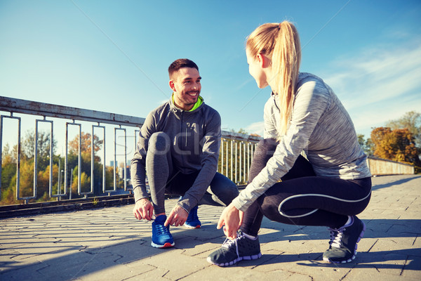 smiling couple tying shoelaces outdoors Stock photo © dolgachov