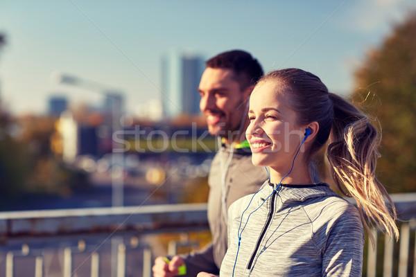 happy couple with earphones running in city Stock photo © dolgachov