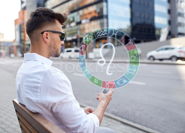 man with smartphone and zodiac signs in city Stock photo © dolgachov