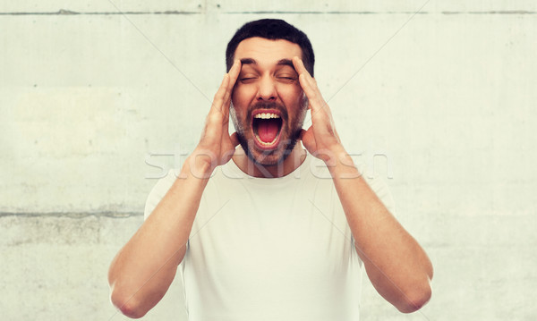őrült kiált férfi póló szürke fal Stock fotó © dolgachov