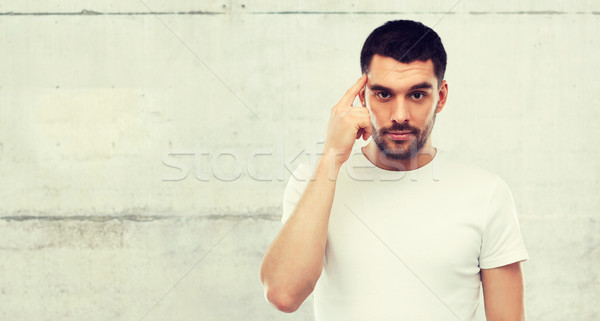 Homem dedo templo cinza parede anúncio Foto stock © dolgachov