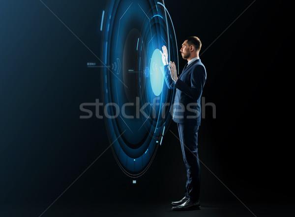 businessman with virtual projection over black Stock photo © dolgachov