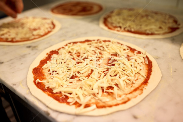 raw pizza with grated cheese on table at pizzeria Stock photo © dolgachov