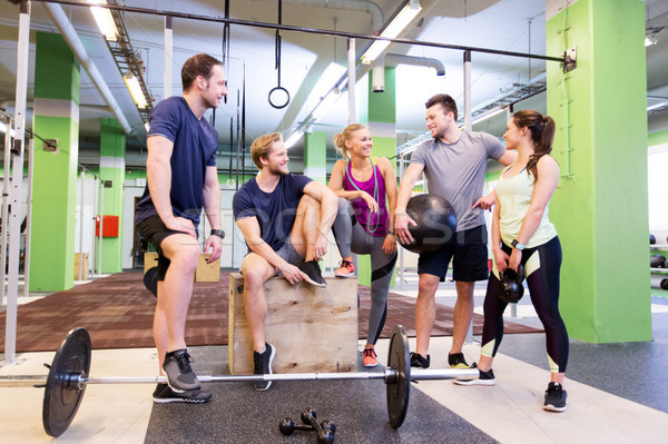 group of friends with sports equipment in gym Stock photo © dolgachov