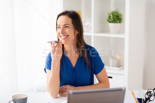 woman using voice recorder on smartphone at office Stock photo © dolgachov