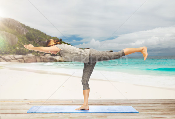 woman doing yoga warrior pose on half-bent outdoor Stock photo © dolgachov