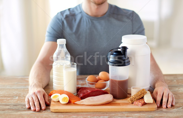 close up of man with food rich in protein on table Stock photo © dolgachov