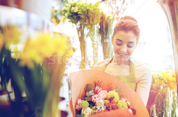 smiling florist woman with bunch at flower shop Stock photo © dolgachov