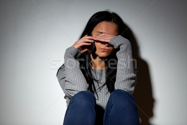 unhappy woman crying and calling on smartphone Stock photo © dolgachov