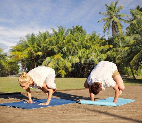 couple making yoga crow pose outdoors Stock photo © dolgachov