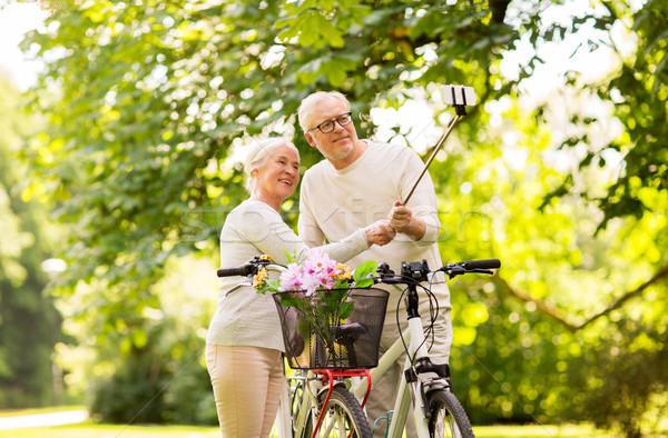senior couple with bicycles taking selfie at park Stock photo © dolgachov